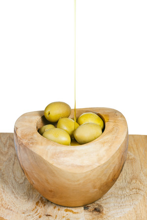 olive oil in thin trickle flows on olives in wooden bowl close up isolated on white background photo