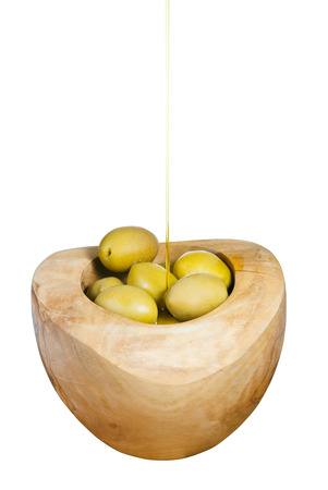 trickles: olive oil trickles on green olives in wooden bowl close up isolated on white background