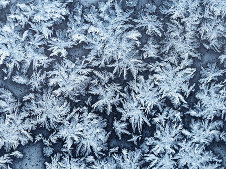 window pane: snowflakes and frost pattern on window pane in cold winter evening close up Stock Photo
