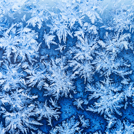 snowflakes and frost pattern on window glass in cold winter evening close up photo