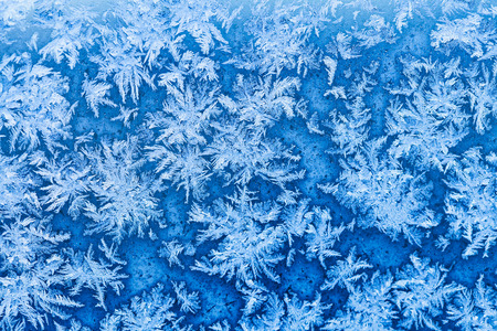 snowflakes and frost pattern on window in cold winter evening close up photo
