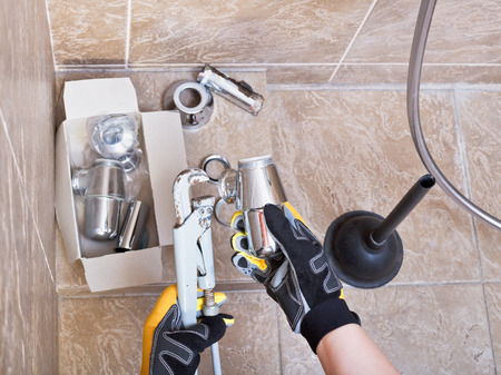 plumber repairs sink chrome plated trap in bathroom photo