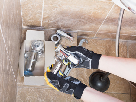 replaces: Sanitary technician replaces plumbing trap of sink in bathroom