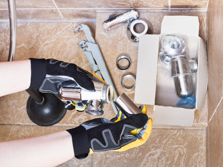 replaces: plumber replaces chrome plated trap of sink in bathroom