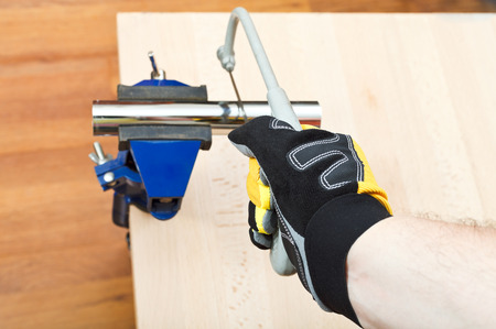 vise grip: plumber sawing plumbing drain pipe gripped in vice on wooden table by hacksaw
