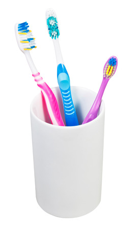 one children and two adult toothbrushes in ceramic glass - family set of toothbrushes isolated on white background photo