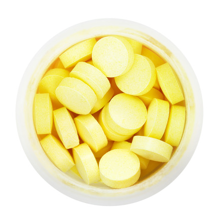 pillbox: top view of yellow pills in round plastic bottle isolated on white background Stock Photo