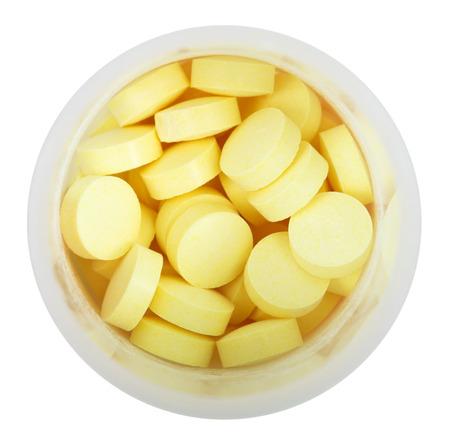 pilule: Pillole gialle in bottiglia di plastica rotondo vicino isolato su sfondo bianco