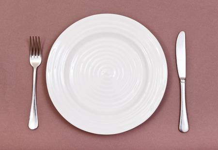フォークとナイフの茶色の背景の設定空の白いプレートのトップ ビュー