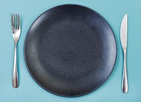 bovenaanzicht van lege zwarte plaat met vork en mes op groene achtergrond