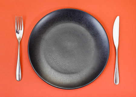 top view of empty black plate with fork and knife set on red background photo