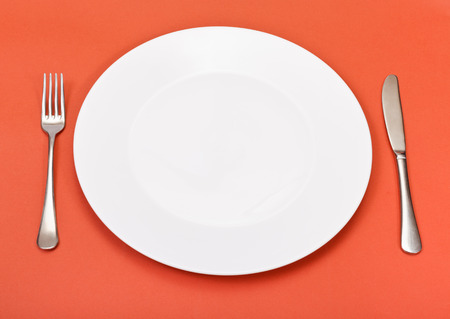 above view of empty white porcelain plate with fork and knife set on red background photo