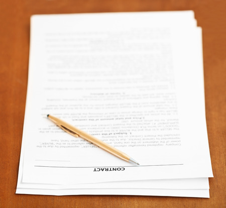 conclude: three pages of sales contract and golden pen on wooden table