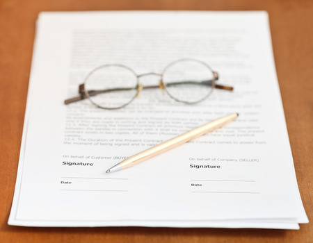 pages of sales contract, golden pen and eyeglasses on wooden table photo