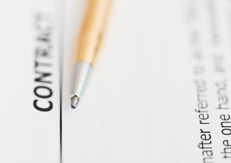 conclude: contract and tip of golden pen close up