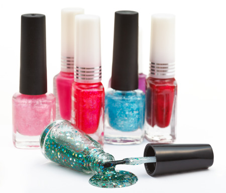 lacquer: set of nail polish bottles and spilled green lacquer on white Stock Photo