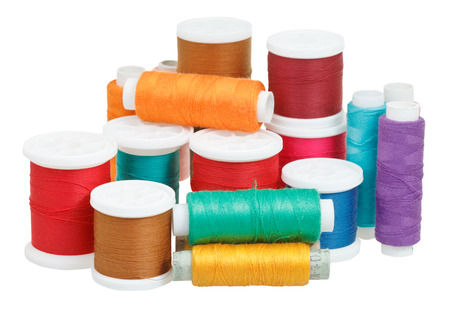 sartorial: multicolored thread bobbins isolated on white background