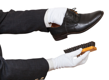 Shoeshiner in white gloves cleaning black shoes by brush isolated on white background photo