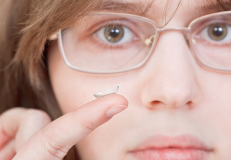 contact lenses: girl with glasses holds contact lens on your finger near the eyes