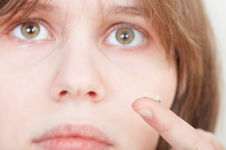 myopic: girl holds contact lens on your finger near the eyes
