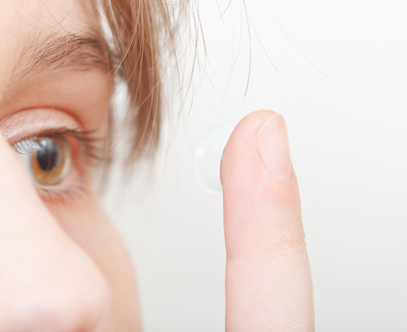 inserts: young woman inserts contact lens in eye close up