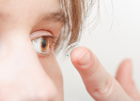 corrective: young woman inserts corrective lens in eye close up