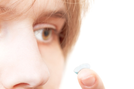 myopic: girl removes contact lens from eye close up