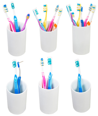glases: collection of toothbrushes in ceramic glases isolated on white background