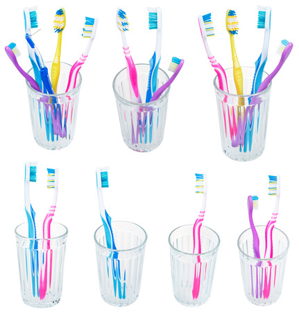 collection of toothbrushes in glases isolated on white background photo