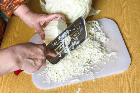 shredding: woman shredding cabbage on cutting board on table