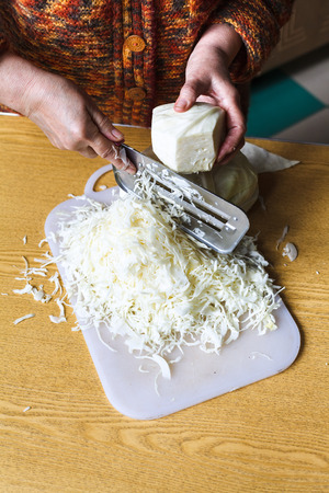 shredding: woman shredding cabbage by manual slaw cutter on table
