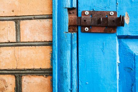pawl: chiusura in metallo chiuso su blu dipinto porta woooden vicino