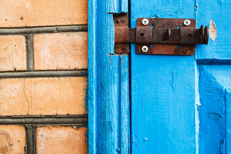 closed metal latch on blue painted woooden door close up photo