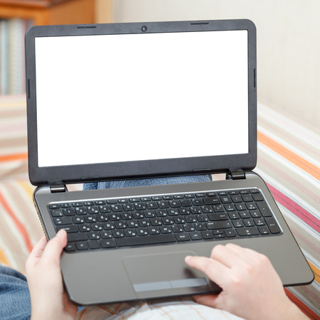 computer devices: man uses laptop with cut out screen in living room Stock Photo