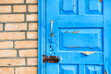 details of closed shabby blue wooden door in brick wall photo