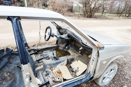 disassembled: old disassembled car on country road in spring Stock Photo