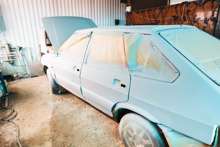 private parts: painting of old car in small country workshop