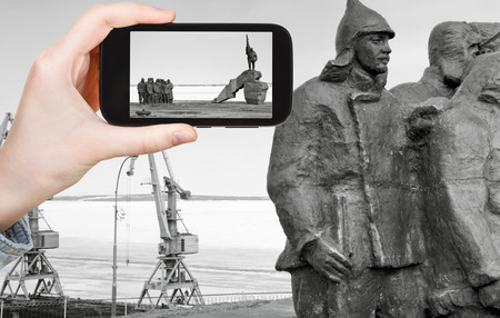 committee: travel concept - tourist taking photo of Memorial First Revolutionary Committee (Revcom) of Chukotka on mobile gadget, Anadyr, Russia