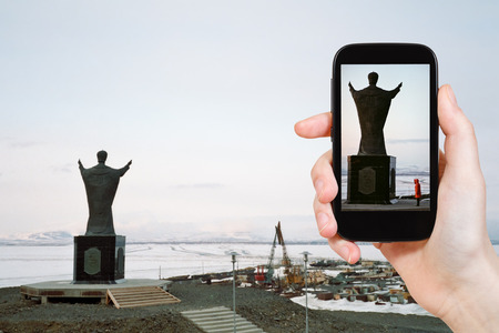 'saint nicholas': travel concept - tourist taking photo of Monument Saint Nicholas on Andyrsky liman in Chukotka on mobile gadget, Anadyr, Russia Stock Photo
