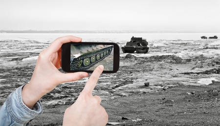 tracked: travel concept - tourist taking photo of tracked vehicle on ice road on mobile gadget, Anadyr, Chukotka, Russia