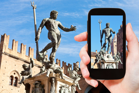 neptun: travel concept - tourist snapping photo of fountain of neptune in Bologna on mobile gadget, Italy