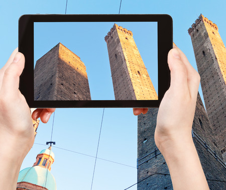torri: travel concept - tourist taking photo Due Torri Two Towers in Bologna city of on mobile gadget, Italy