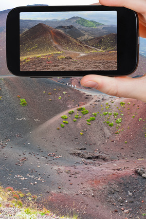 volcano slope: travel concept - tourist taking photo of path on slope of craters volcano Etna on mobile gadget, Sicily, Italy