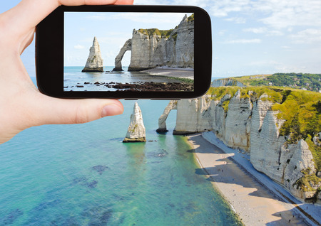 english channel: travel concept - tourist taking photo of english channel coast with cliffs on Etretat cote dalbatre, France on mobile gadget