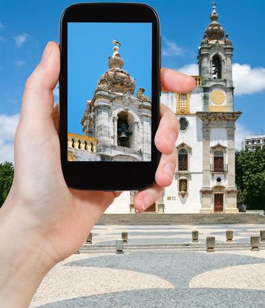 carmo: travel concept - tourist taking photo of The Igreja do Carmo (Carmo Church) in Faro, Portugal on mobile gadget Stock Photo