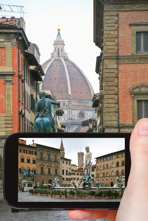 travel concept - tourist taking photo of Piazza della Signoria in Florence on mobile gadget, Italy photo