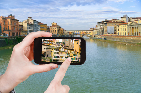 travel concept - tourist taking photo of Ponte Vecchio on Arno river in Florence on mobile gadget photo