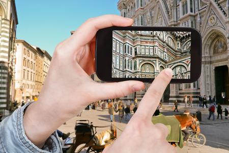 santa maria del fiore: travel concept - tourist taking photo of The Basilica di Santa Maria del Fiore in Florence on mobile gadget, Italy