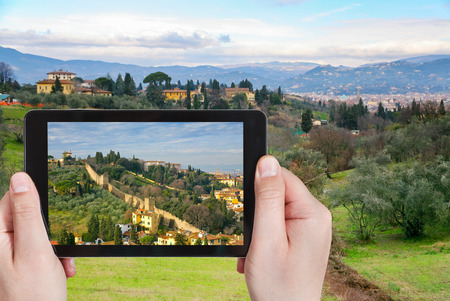 travel concept - tourist taking photo of green hills in Tuscany on mobile gadget, Florence, Italy photo