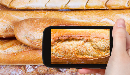 photographing food concept - tourist taking photo of fresh baked loaves of bread on mobile gadget, France